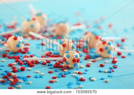 Delicious lollipops and scattered sprinkles on blue wooden background