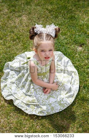 little dissatisfied girl in a dress with two bows sitting on the grass. her face unhappy. Girl tired. top view
