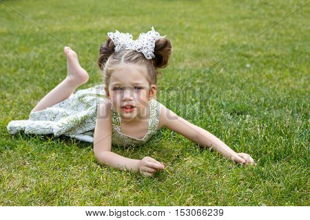 beautiful little girl in a yellow dress and with a bow in her hair lying on the grass. girl smiling