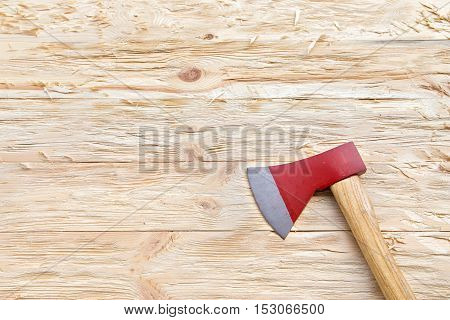 Red ax on a wooden background top view
