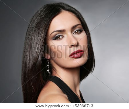 Portrait of beautiful woman with trendy makeup on grey background