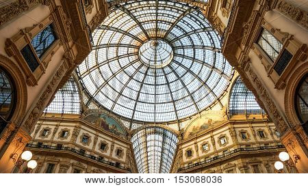 October 23 2015 - Milan Lombardy Italy : Low angle view toward circular domed ceiling and windows inside the Vittorio Emanuele Milan shopping mall interior