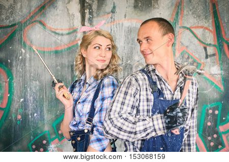 Portrait of a young man and woman in overalls with tools for the repair of the interior in hands. Concept of construction and home repair.