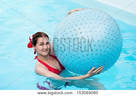 Young beautiful girl with blue ball in swimming pool.