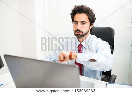 Impatient businessman snorting while watching his wrist watch