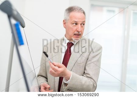 Businessman explaining data on a white board