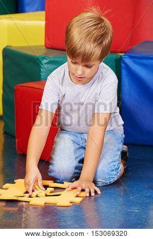 Boy playing with a big jigsaw puzzle in kindergarten