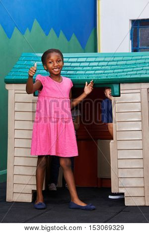 African girl holding thumbs up in kindergarten in front of a playhouse
