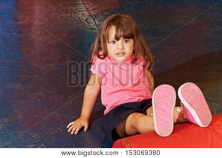 Little child doing children sports in gym with her legs on a pillow
