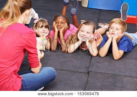 Children listening to story from book read by nursery teacher in kindergarten