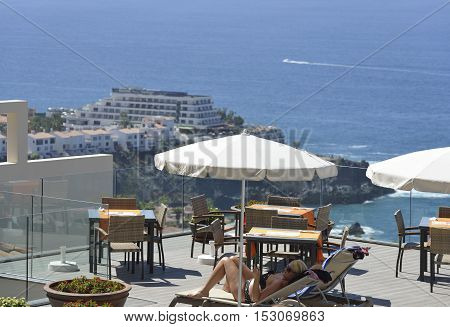 LOS GIGANTES, CANARY ISLANDS, SPAIN - OCTOBER 16: Mature blonde woman in swimsuit is reading lying in shadow under parasol on outdoor area cafe on October 16, 2016 in Los Gigantes, Tenerife Island, Canary Islands, Spain.Gigantes resort on blue ocean water