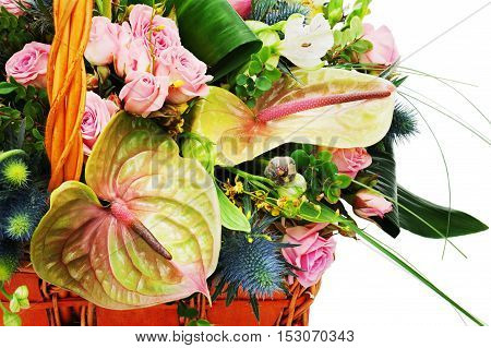 Fragment of flower bouquet arrangement centerpiece in a wicker gift basket isolated on white background.
