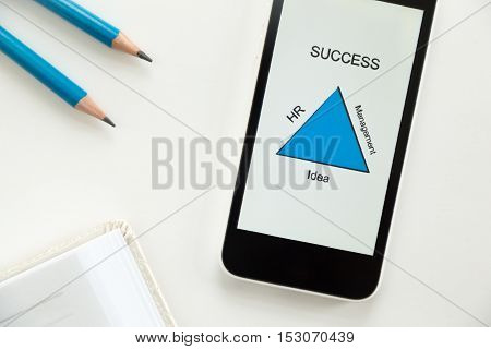 Top view of a mobile phone lying on a white office desk, success diagram on the screen, part of a notebook, sharp pencils, blue color. Business concept, lay flat
