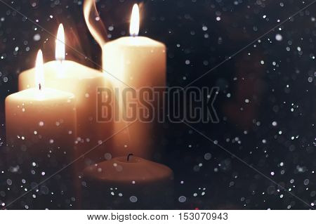 bright flame of a burning candle on a black background on the eve of New Year holidays