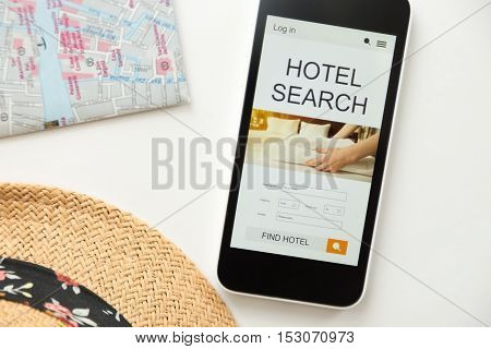 Top view of a mobile phone lying on a white office desk, hotel search on the screen, part of a map, straw hat. Tourism concept