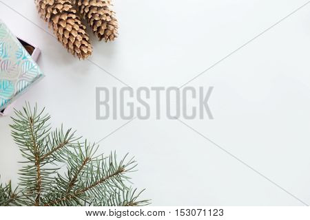 Flat view of Christmas decoration, cones, fir tree branch, gift box. Space for a text or design in the right. Christmas concept, copy space