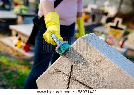 Woman Cleans A Grave With Brush