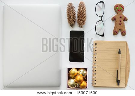 Laptop closed, mobile phone, office supply and Christmas decoration on a white office desk. Flat view, Christmas concept, high angle