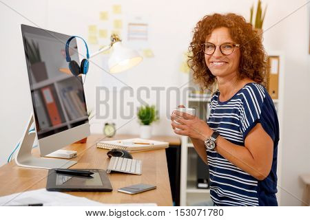 Middle aged woman working on the office and drinking coffee