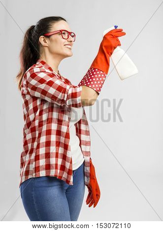 Pretty woman wearing gloves and holding a cleaning spray