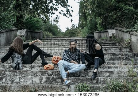 young halloween bearded man with beard and mustache and two girls in black witch hat tights and jeans sit on stony stairs with traditional autumn holiday symbol of orange spooky pumpkin outdoor
