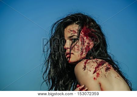 Halloween zombie girl pretty young woman with bloody brunette hair with wounds and red blood outdoors on blue sky