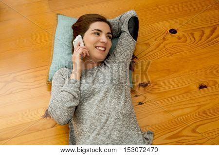 Beautiful woman lying on the floor and talking at phone