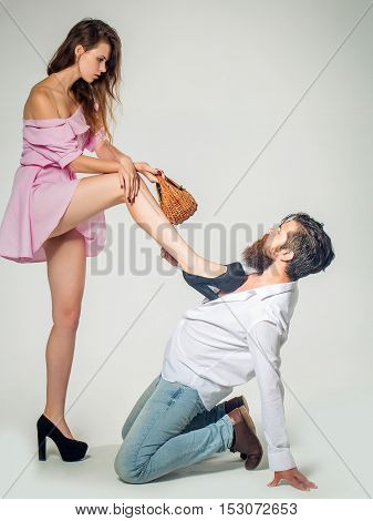 young couple of pretty girl with long hair and sexy body holding basket and handsome bearded man with beard holding flower bouquet sitting on knees makes proposal isolated on white