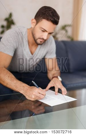 Young man filling model release on glass desk indoor