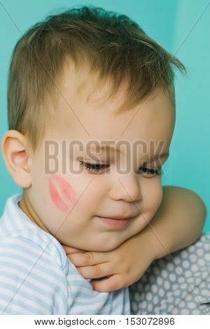 Adorable baby blond boy kid child with red kiss trace on cheek and cute smile on blue wall