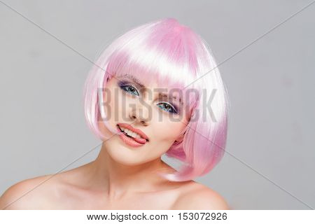 sexy glamour girl or woman with fashionable makeup on pretty face and short hairstyle or pink wig in studio on light background