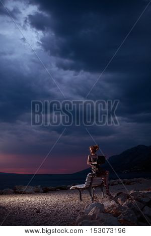 pretty sexy woman or girl with laptop or computer sits on bench outdoor over dark twilight sky with clouds on beach with sea or ocean water on evening natural background copy space