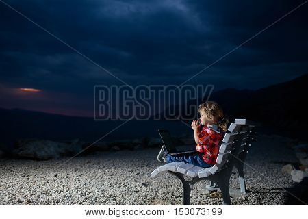 cute baby boy child with laptop or computer on bench outdoor over dark twilight sky with clouds on beach with sea or ocean water on evening natural background copy space