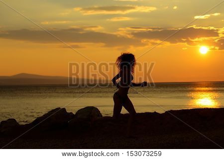 young woman silhouette on beach near sea or ocean water in evening or twilight sunset summer day on natural background
