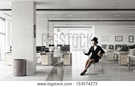 Businesswoman reading on tablet pc . Mixed media