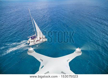 Drone flying above catamaran yacht on open ocean