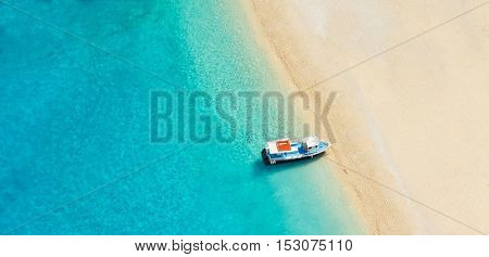 Aerial photo of empty beach with boat anchoring on shore