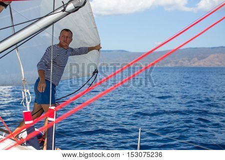 Young man skipper - setting sails on the sailing yacht boat. Vacation, holidays, travel.