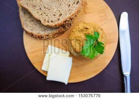 Serve beef pate with a piece of butter and bread on a wooden board, decorated with parsley
