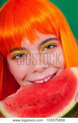 Portrait of red-haired woman in the studio close-up with watermelon.