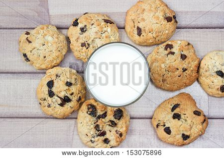 Closeup of homemade moms chocolate cookies with glass of milk on wooden background