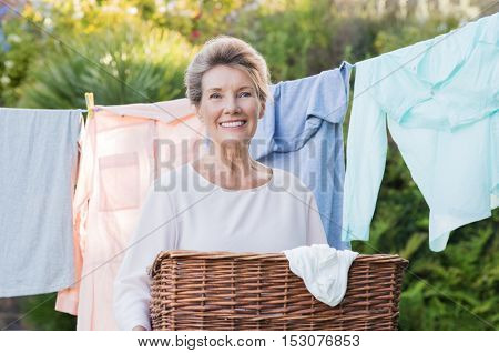 Cheerful senior woman holding laundry basket in front of the clothesline. Portrait of old woman drying clothes. Senior woman hanging clothes out and looking at camera.
