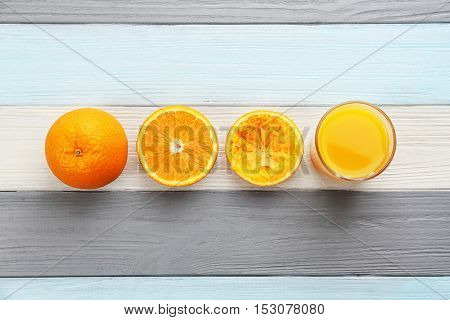 Oranges with juice on wooden table