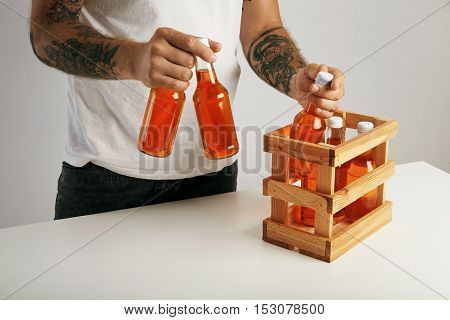 Man In Unlabeled White T-shirt With Box Of Orange Drinks
