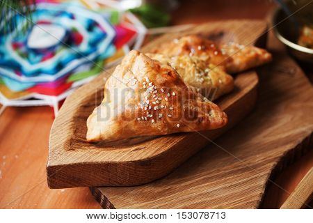 pies samosas with vegetables on a wooden board still life in close-up