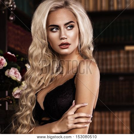 Beautiful sexy long-haired blond woman in black lingerie posing in the interior. The beauty of the face and body. Photos shot in a studio interior