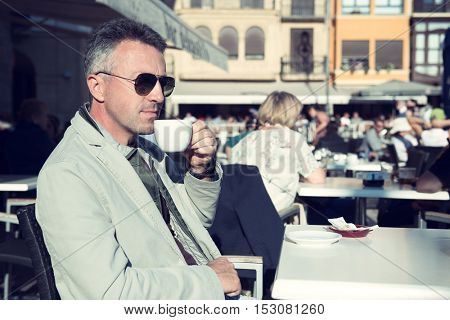 Handsome man drinks coffee in outdoor cafe. Outdoor male portrait, image toned.