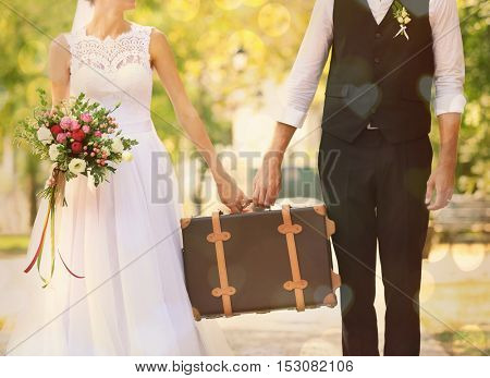 Groom and bride holding vintage suitcase outdoor