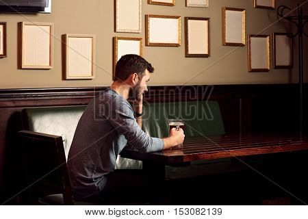 Lonely sad man drinking beer in pub