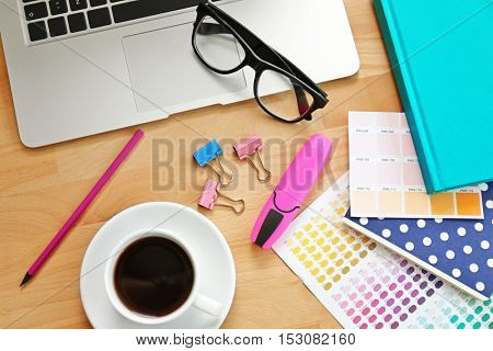 Workplace with laptop and cup of coffee, close up